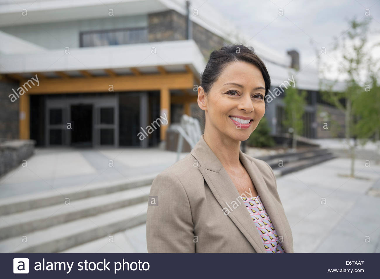 Businesswoman smiling outside office building - Stock Image