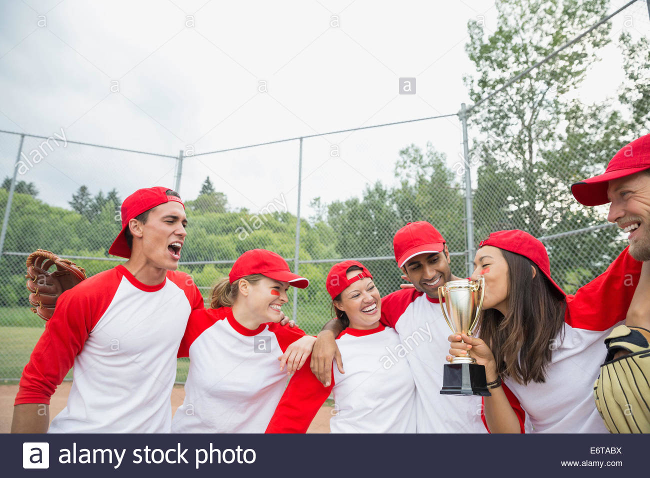 Baseball team cheering with trophy in field - Stock Image