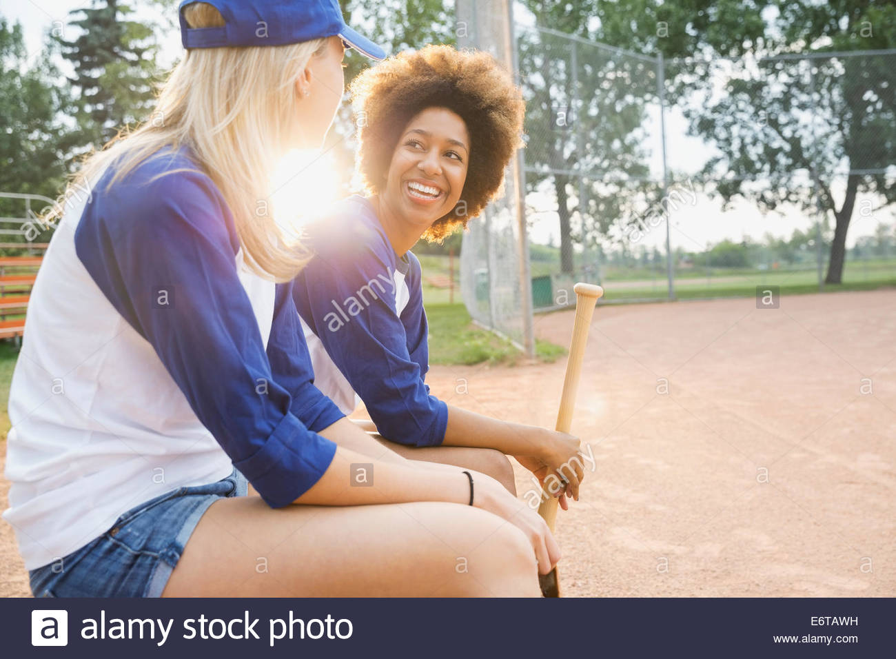 Baseball players sitting on field - Stock Image