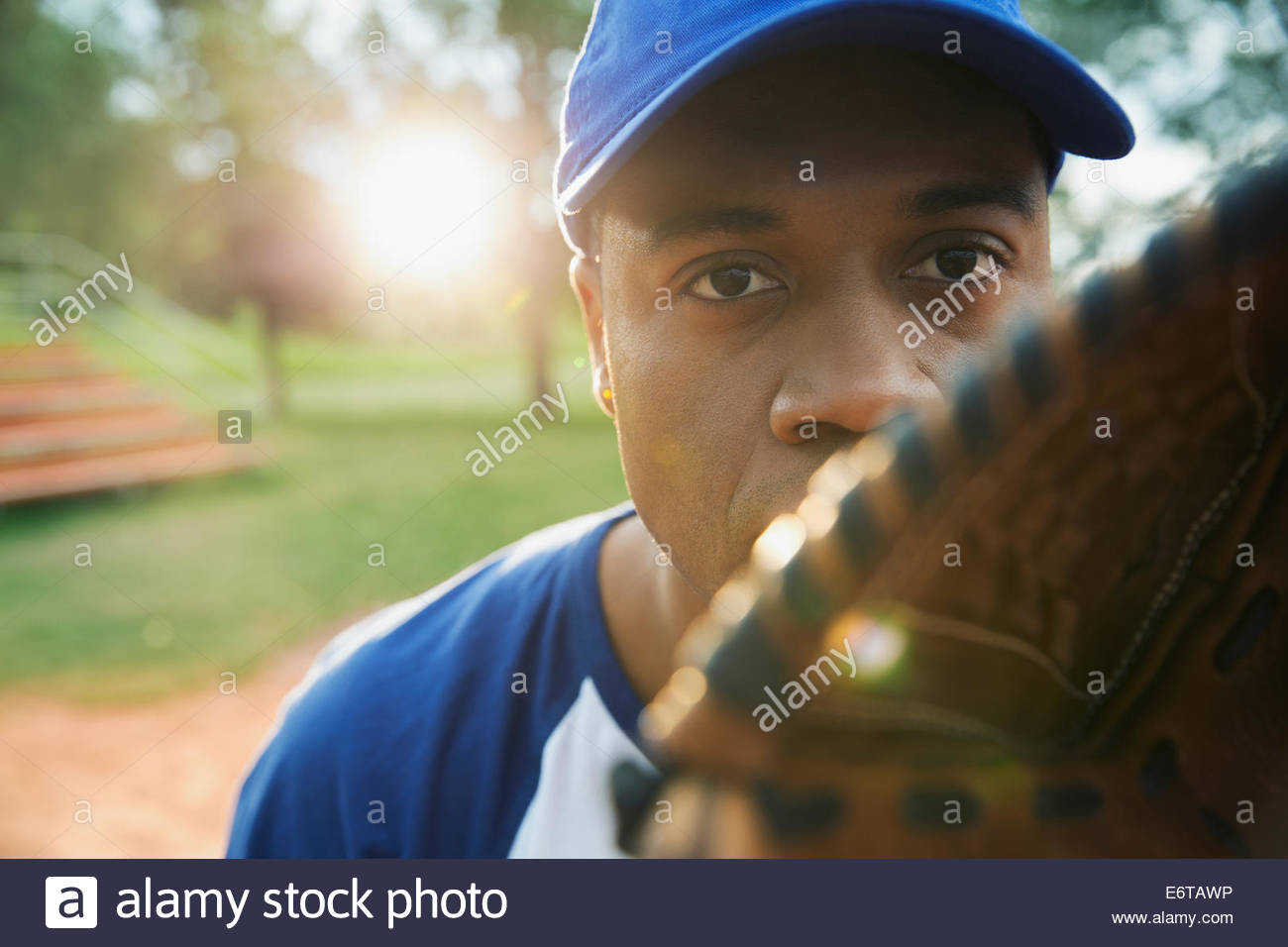 Portrait of serious baseball player holding glove - Stock Image