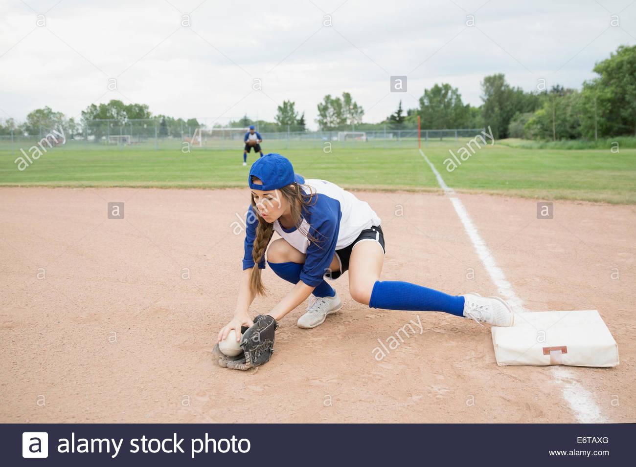 Baseball player scooping up ball at base - Stock Image