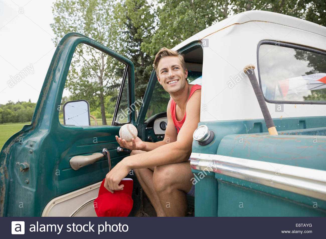 Man sitting in truck in field - Stock Image