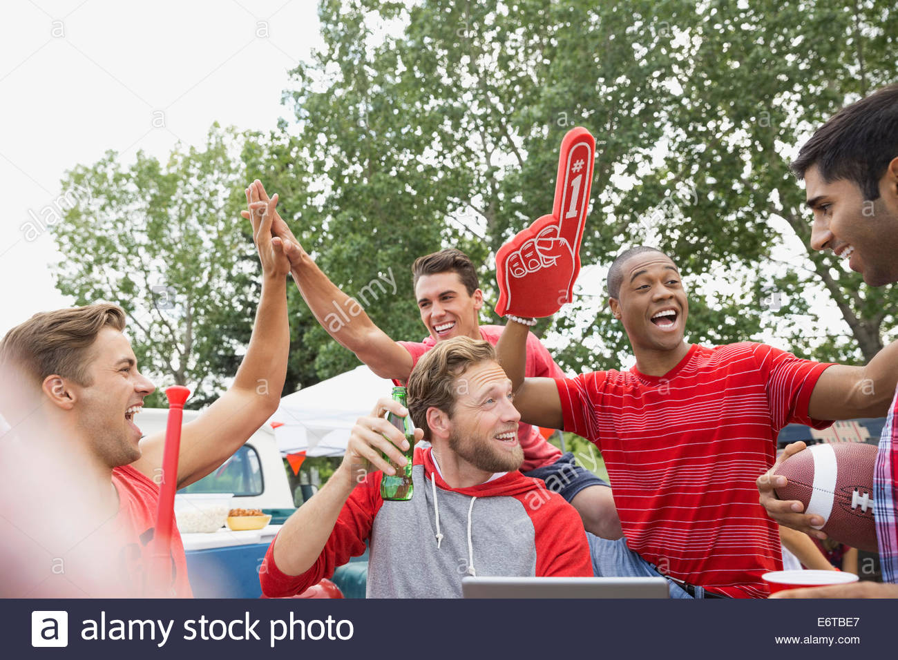 Men cheering at tailgate barbecue in field - Stock Image