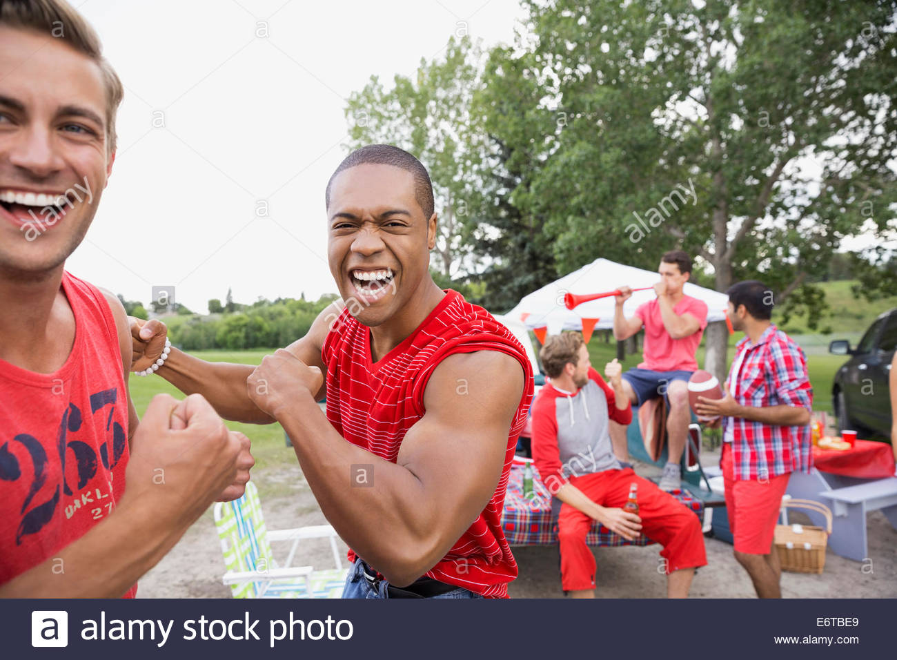 Men laughing at tailgate barbecue in field - Stock Image