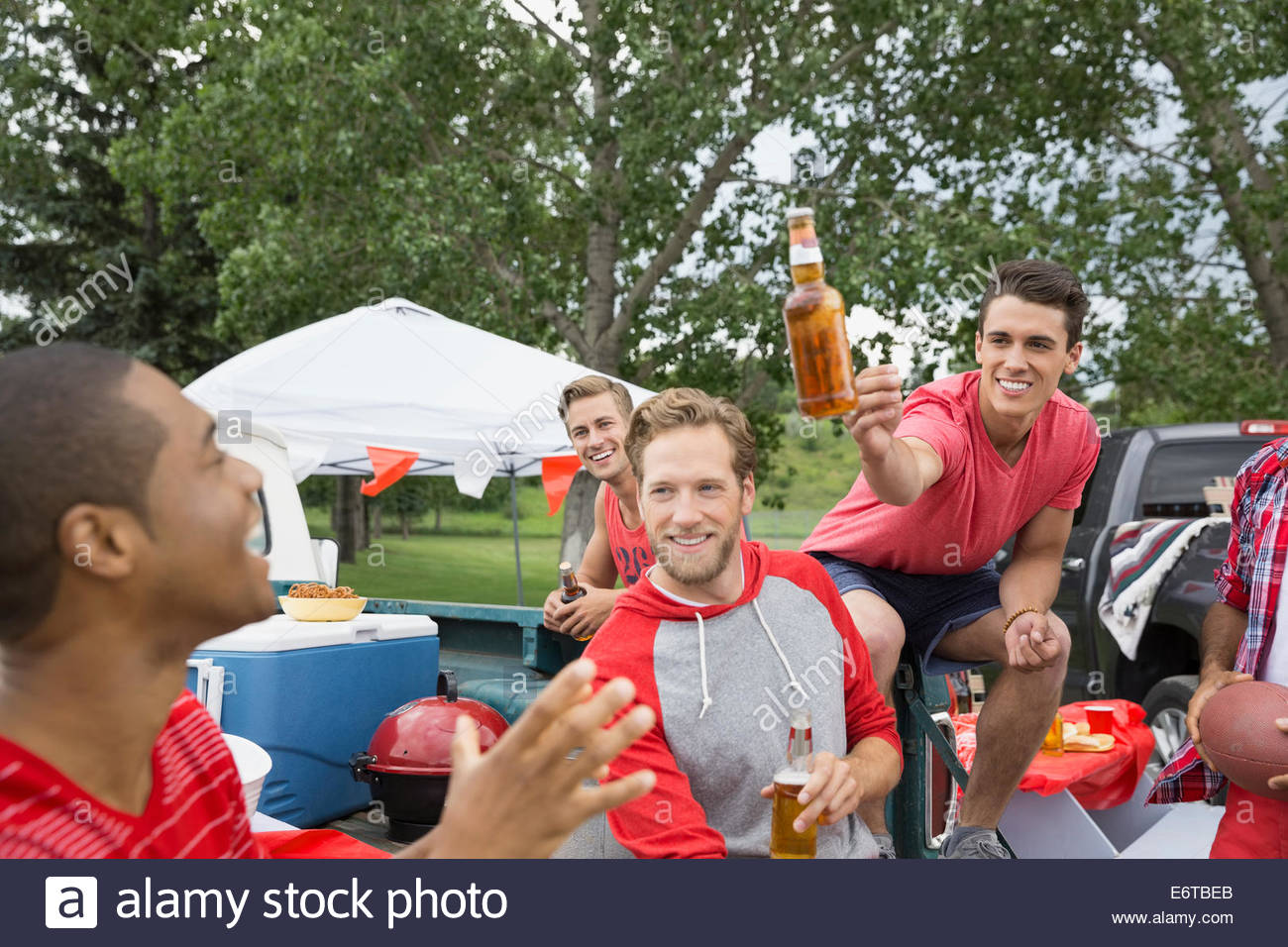 Men drinking beer at tailgate barbecue in field - Stock Image