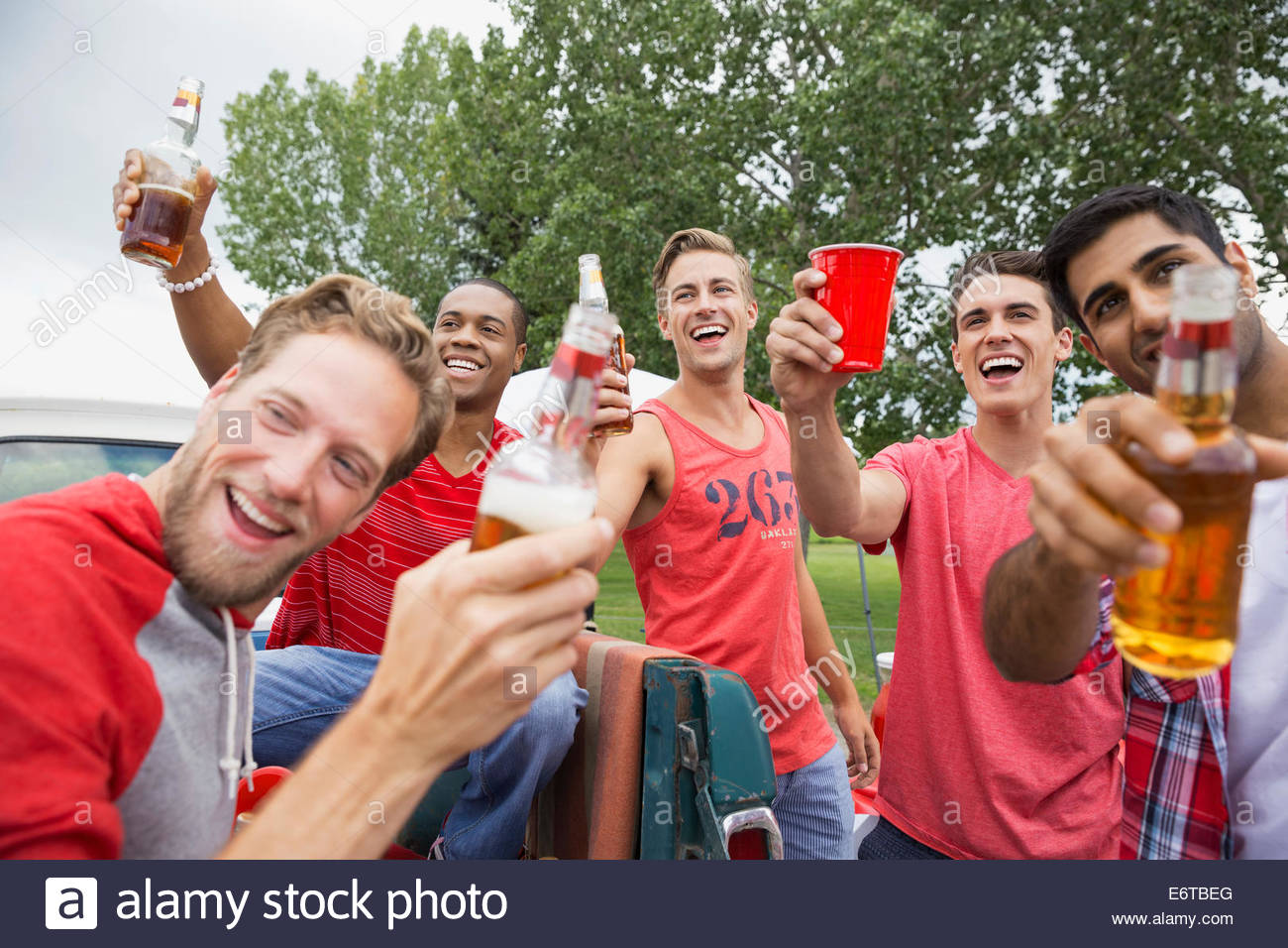 Men toasting each other at tailgate barbecue - Stock Image