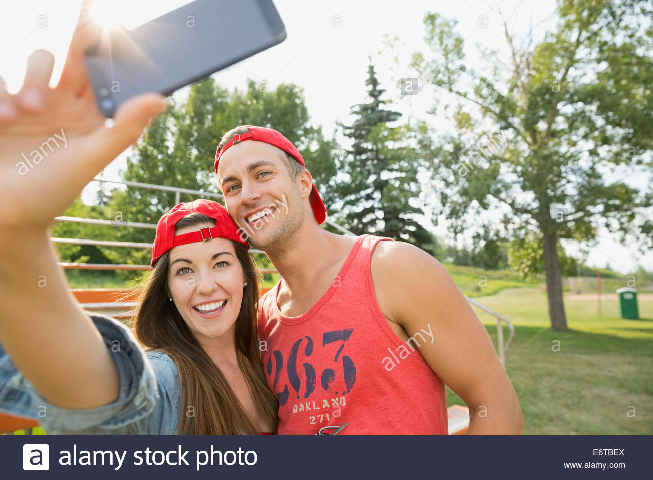 Couple taking cell phone pictures together in field Stock Photo