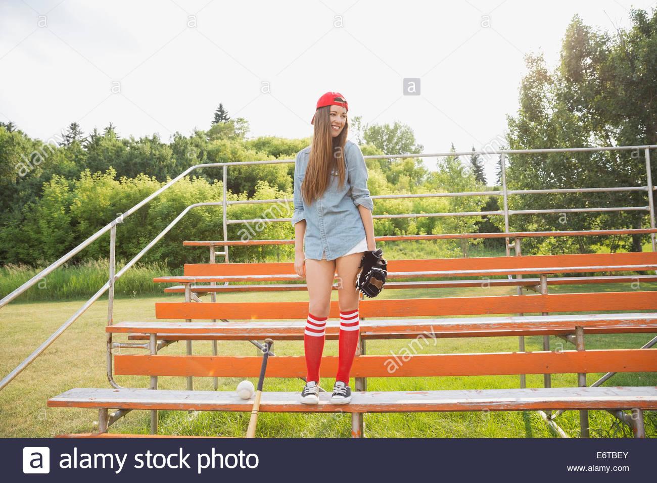 Baseball player standing in bleachers - Stock Image