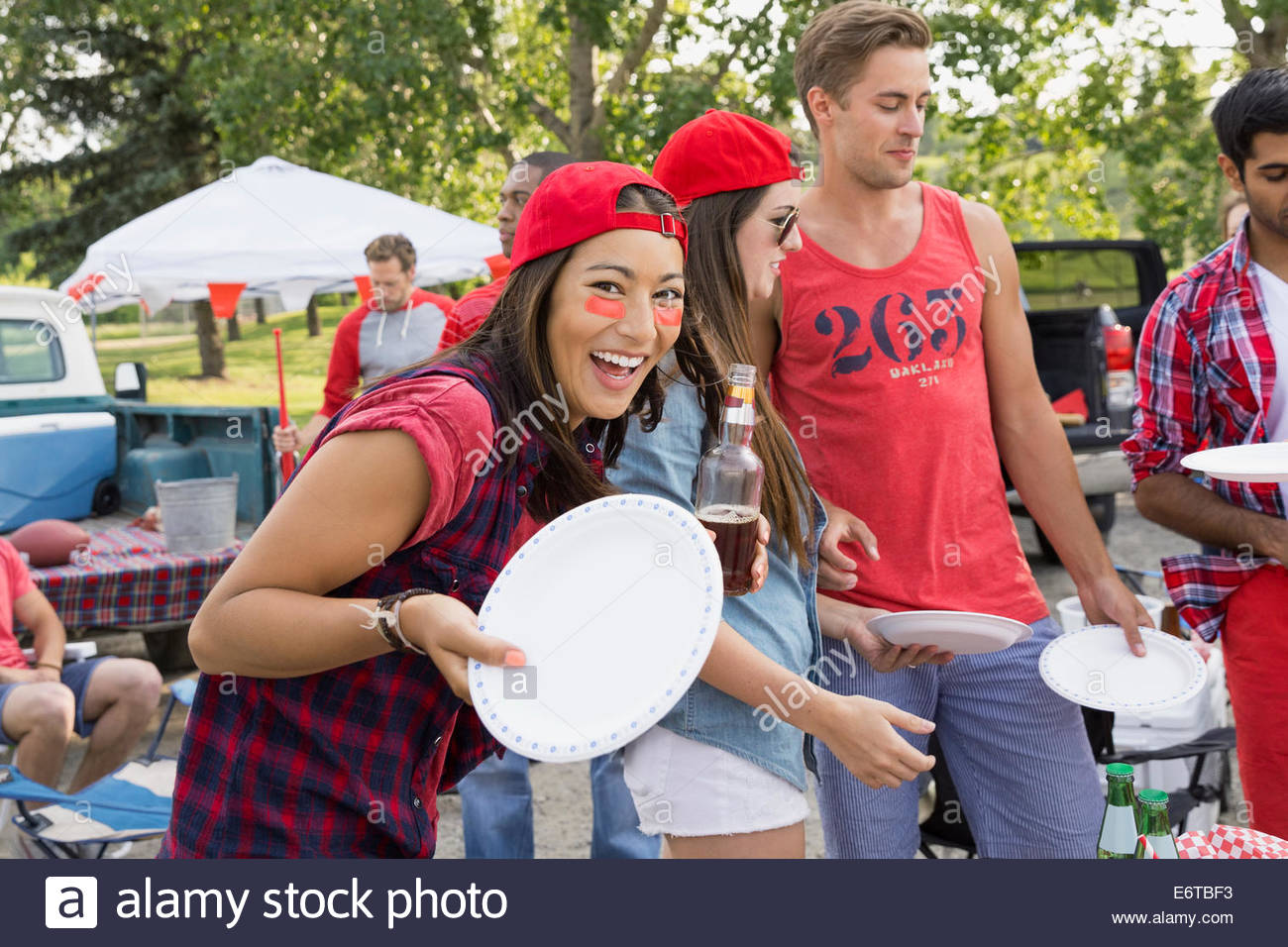 Woman holding plate at tailgate barbecue in field - Stock Image