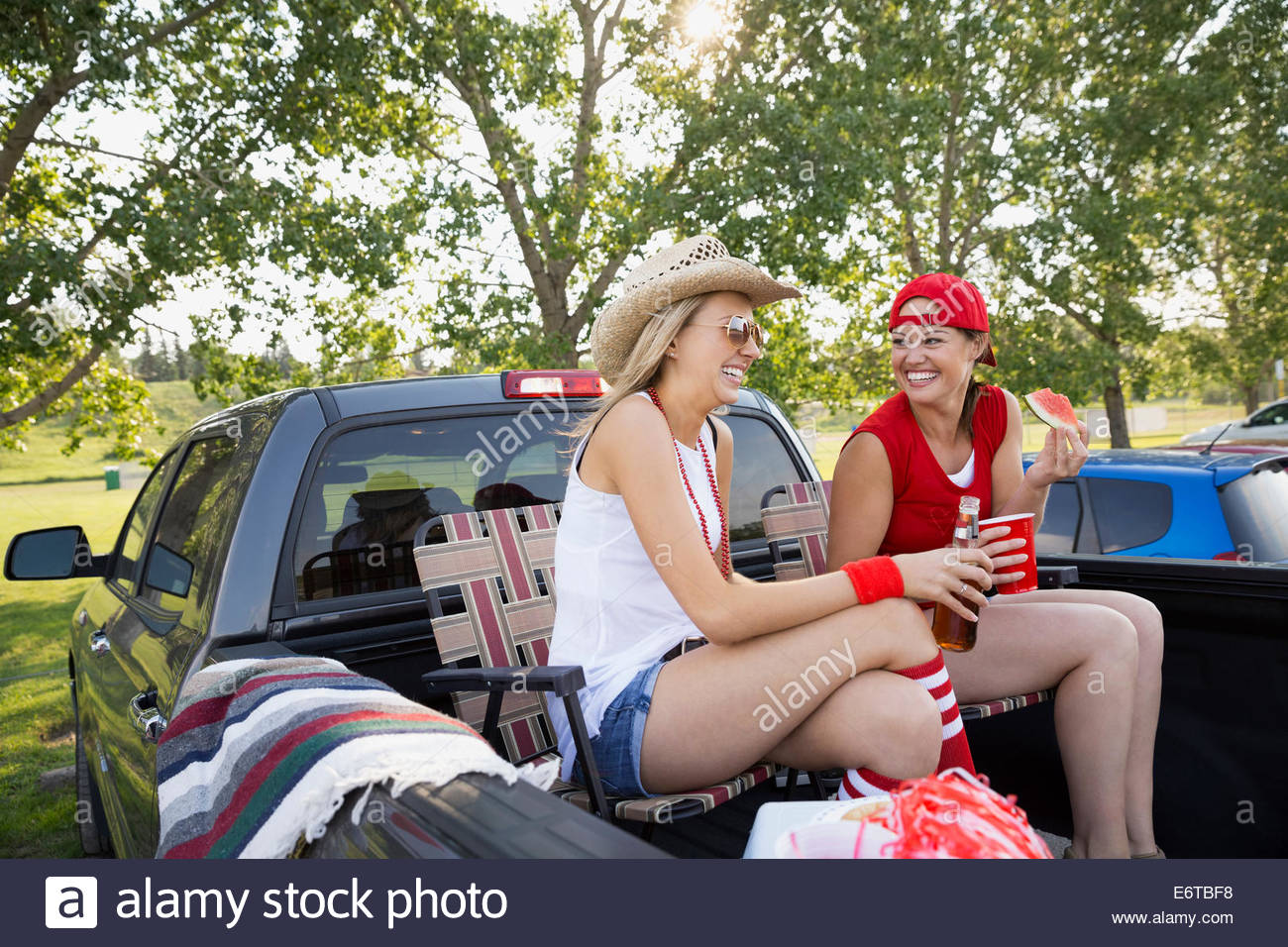 Women relaxing in truck bed at tailgate barbecue - Stock Image