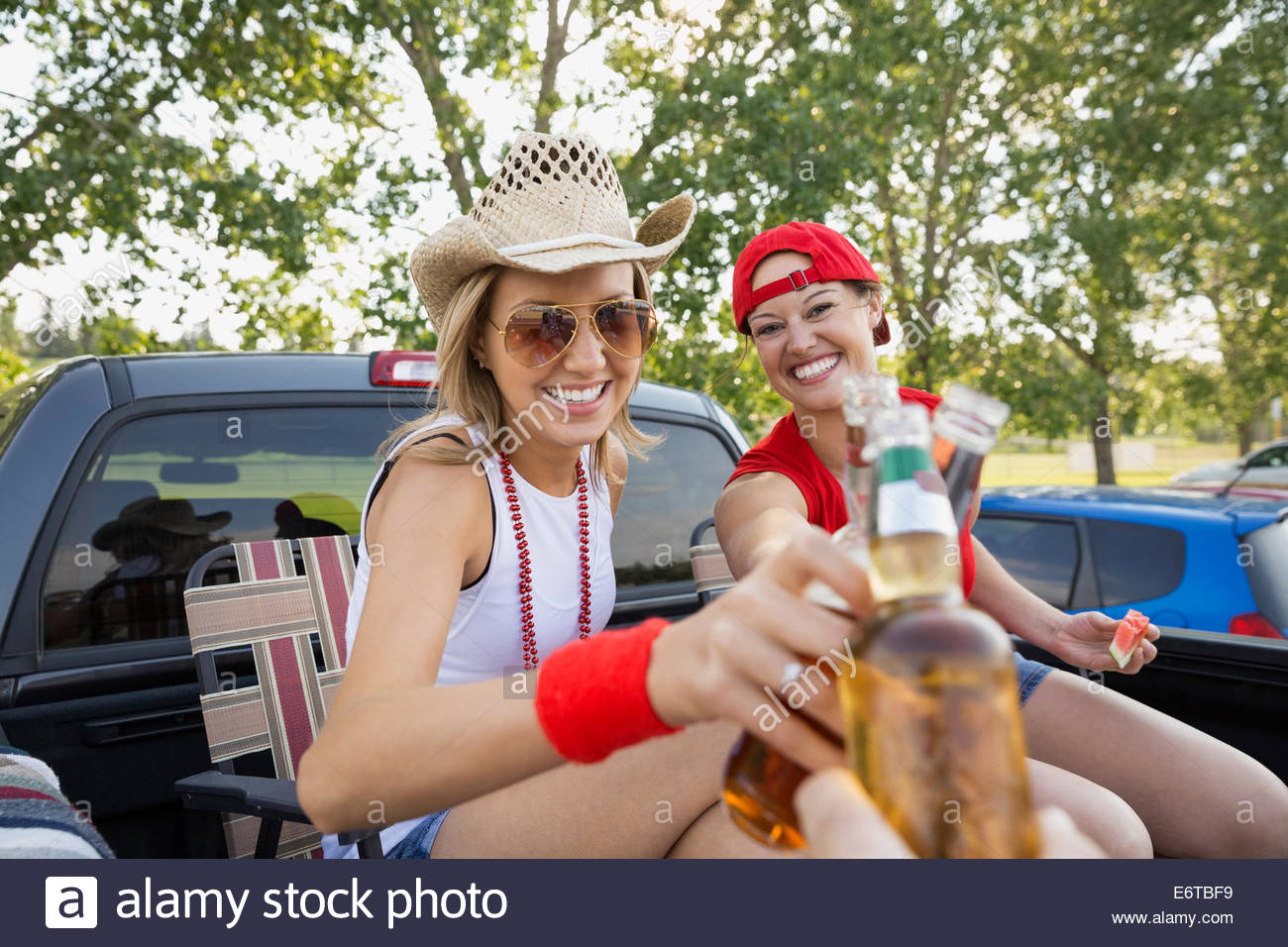 Women toasting each other at tailgate barbecue - Stock Image