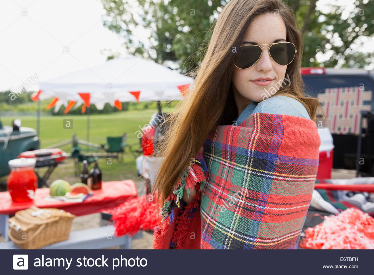 Woman wrapped in blanket at tailgate barbecue - Stock Image
