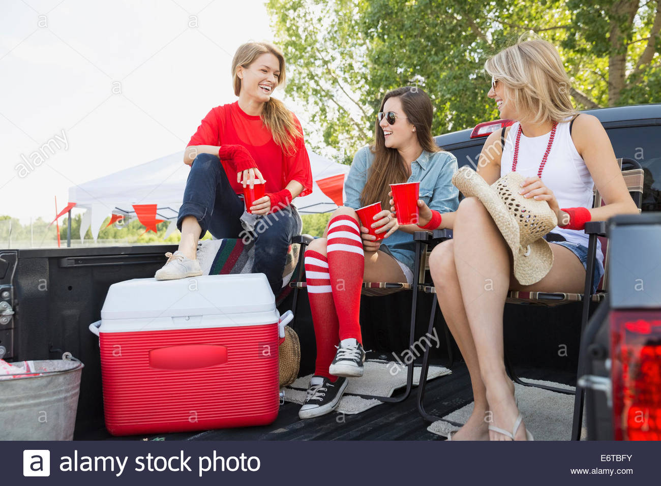 Women relaxing at tailgate barbecue in field - Stock Image