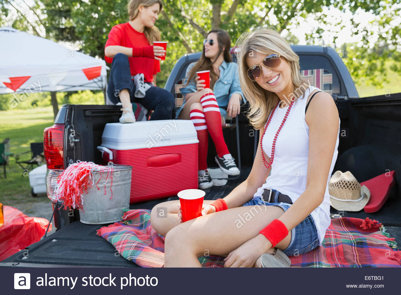Woman relaxing at tailgate barbecue in field - Stock Image