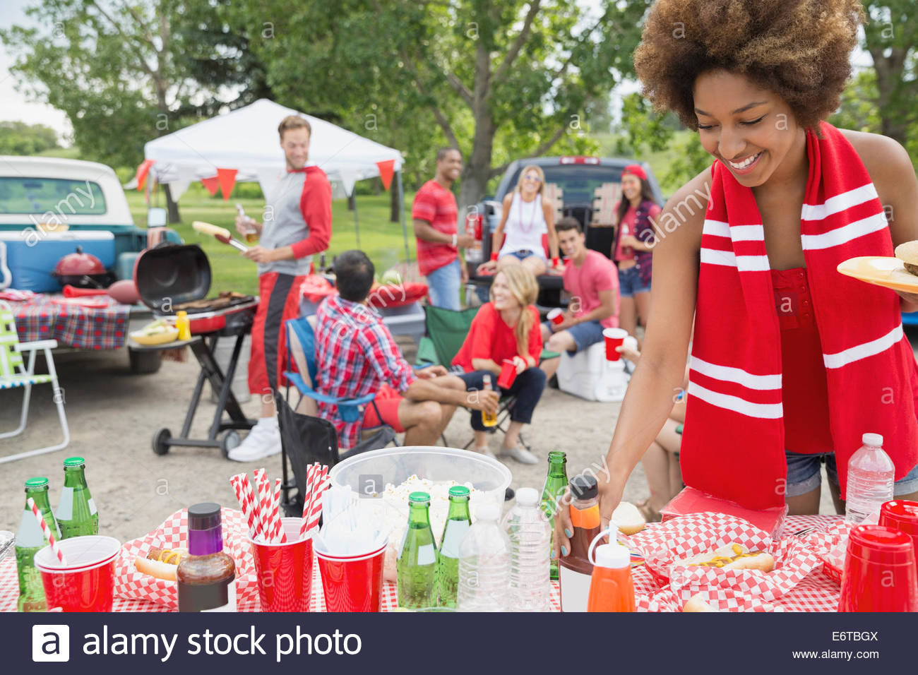 Woman relaxing at tailgate barbecue in fieldStock Photo