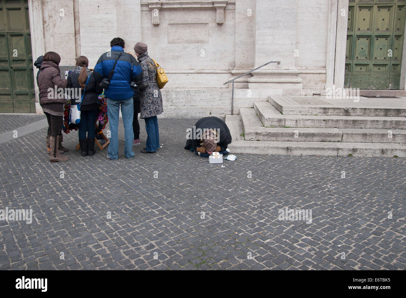 A group of tourists and a female beggar in Rome, Italy. - Stock Image