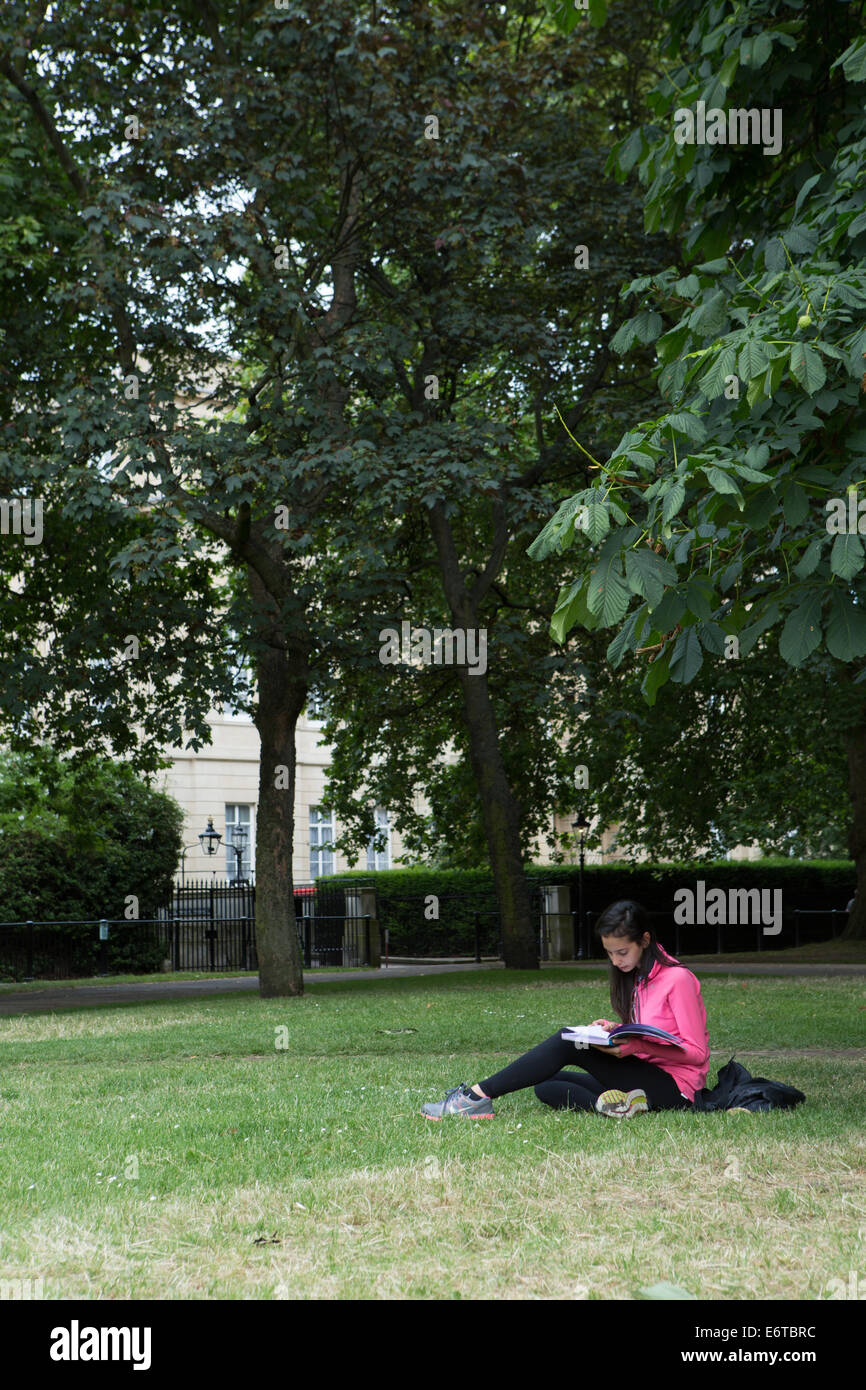A young woman reading a book in Green Park, London - Stock Image