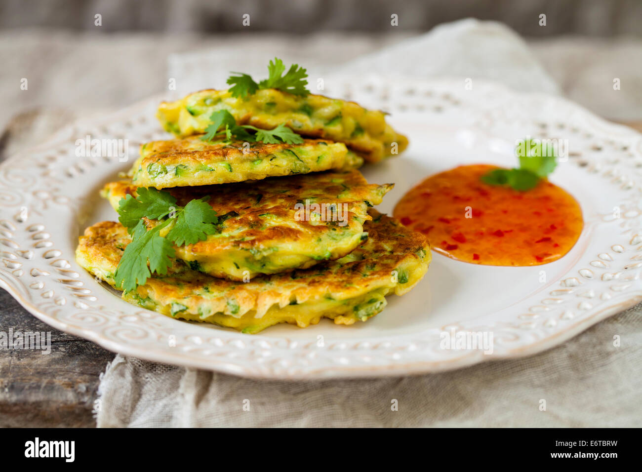 Courgette pancakes with chili sauce - Stock Image