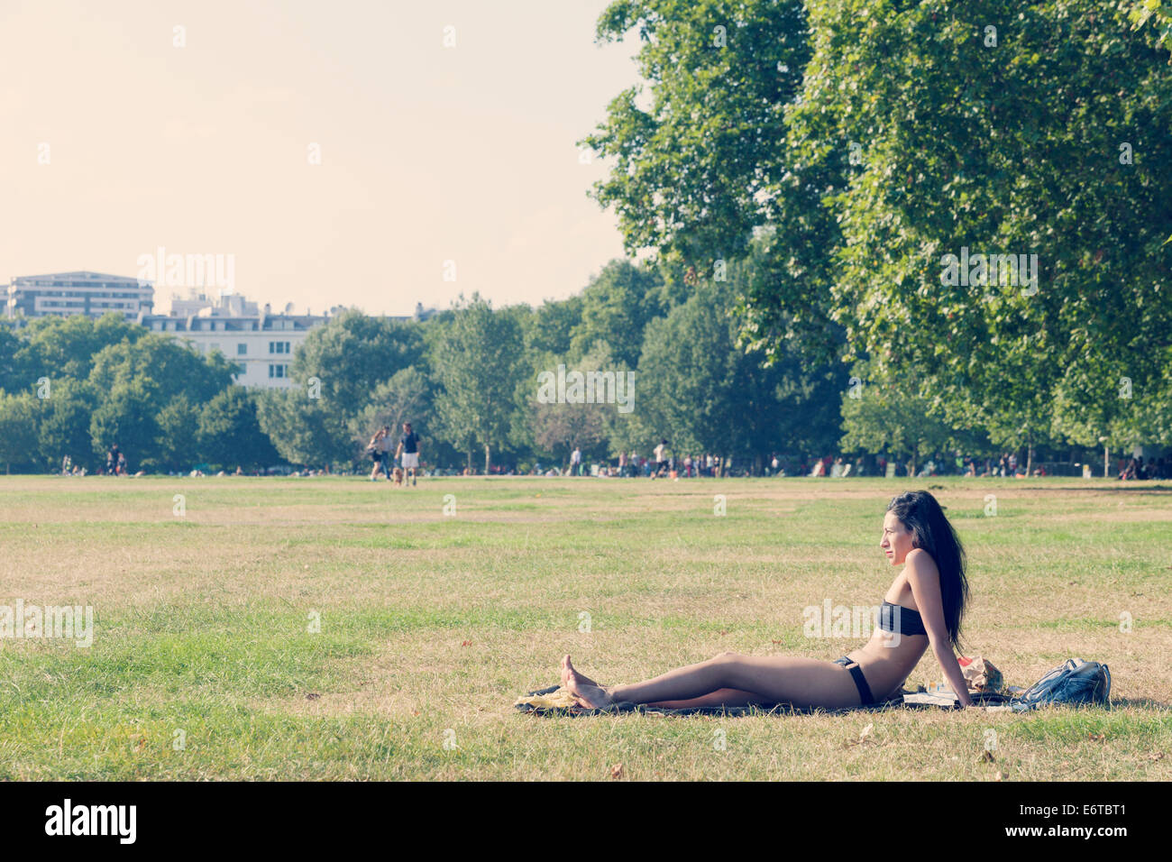 A young woman sunbathing in Hyde Park - Stock Image