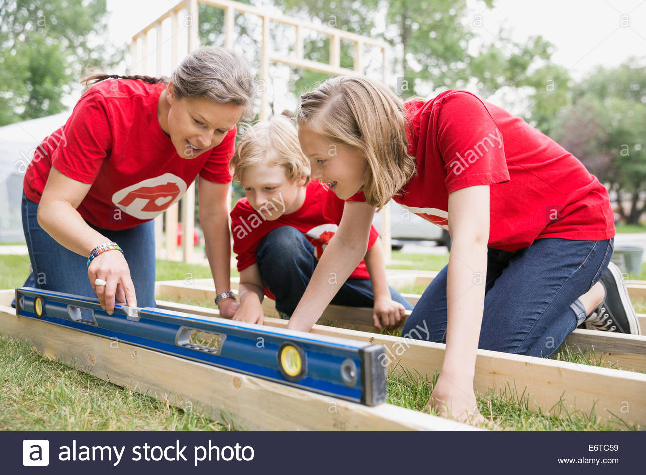 Volunteers using level tool on construction frame - Stock Image