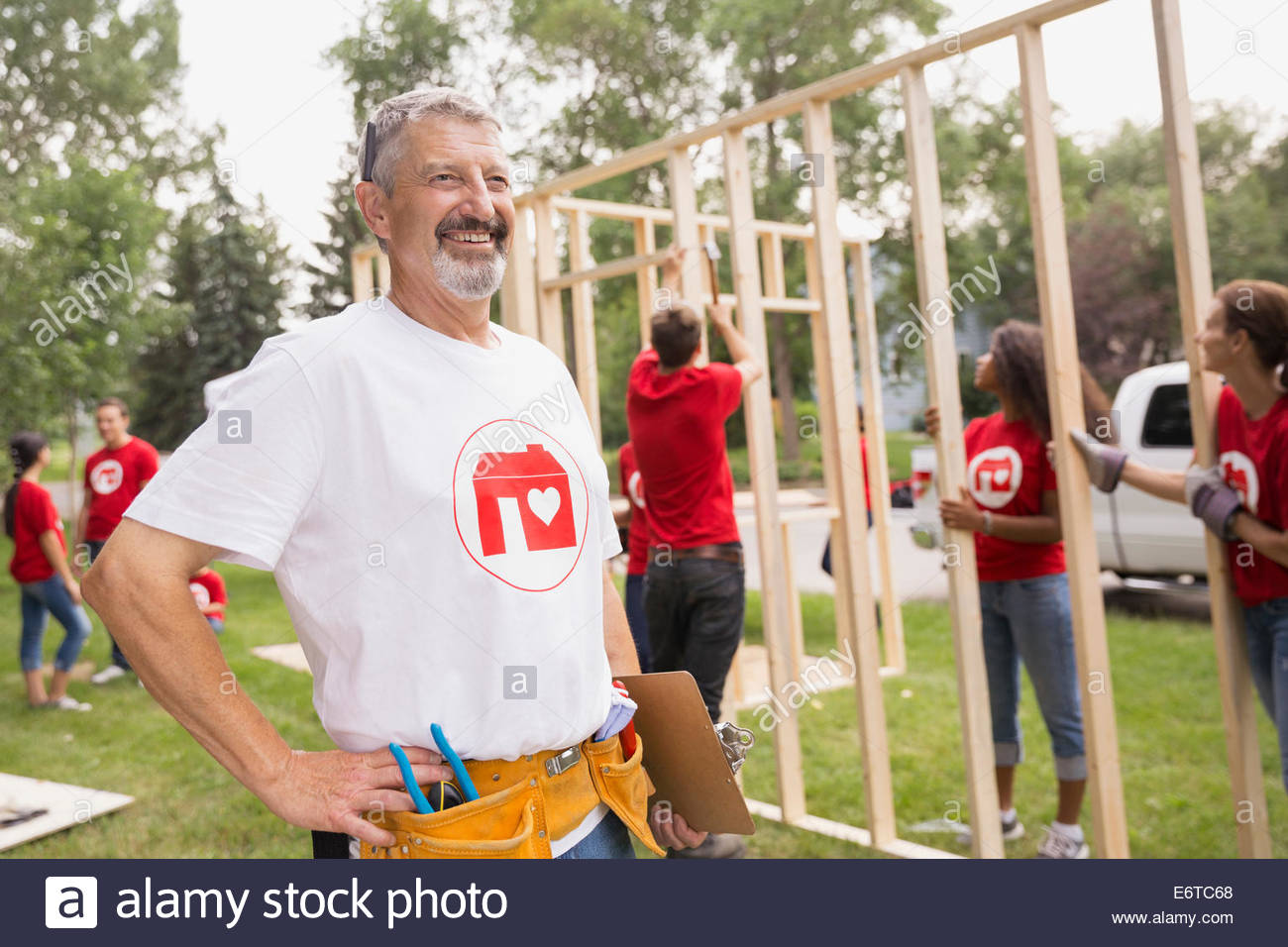 Volunteer with tool belt near construction frame - Stock Image