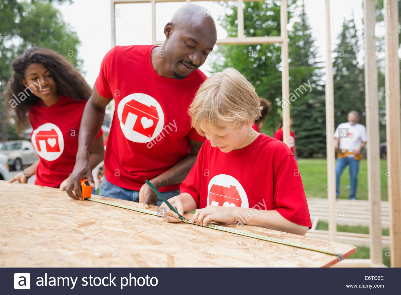 Volunteers measuring construction frame with tape measure - Stock Image