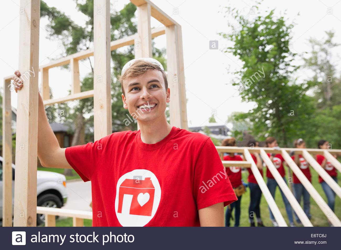 Smiling volunteer at construction frame - Stock Image