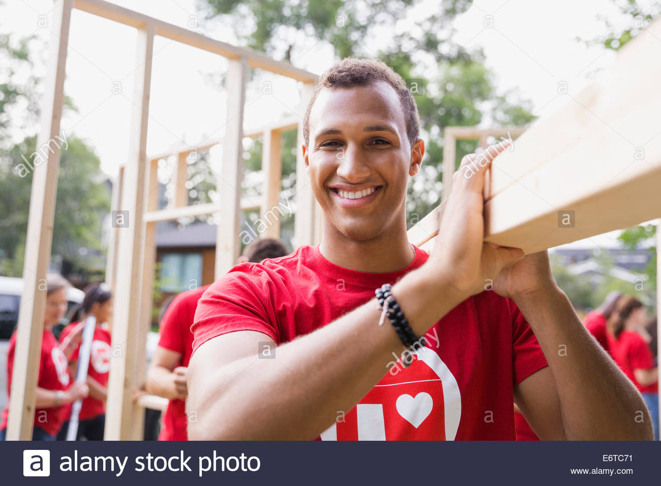 Portrait of smiling volunteer carrying wood - Stock Image