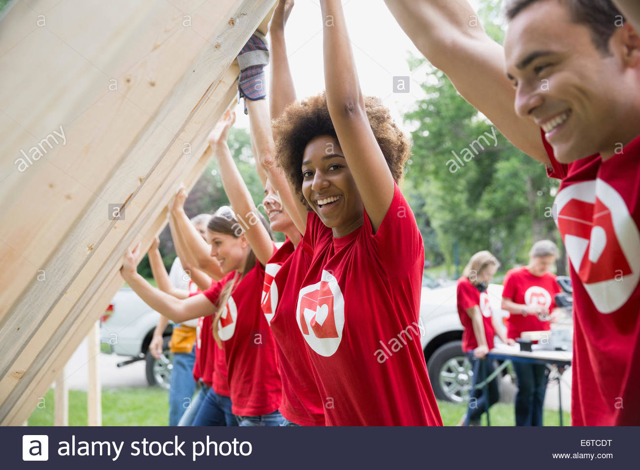 Portrait of smiling volunteers lifting construction frame - Stock Image