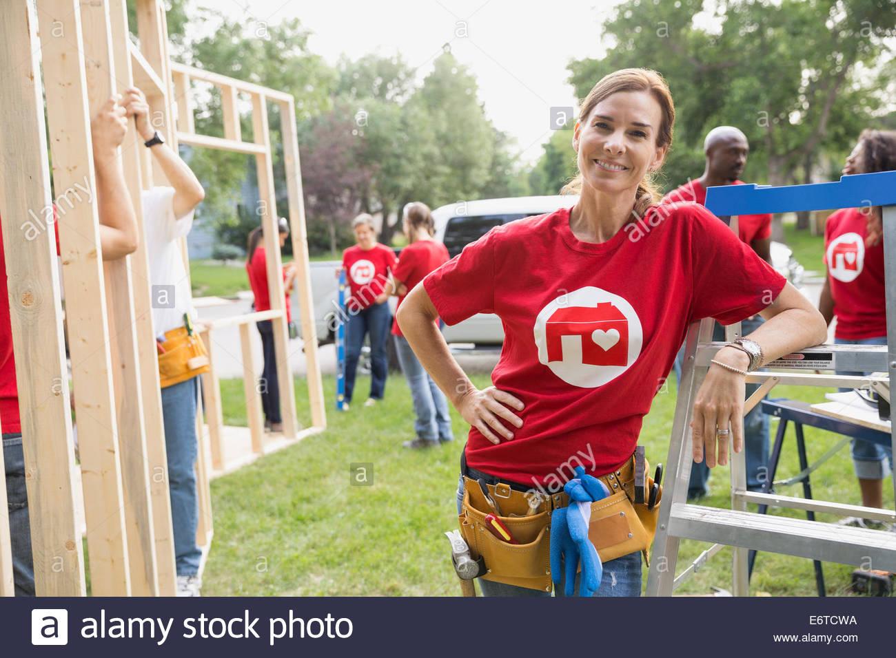 Portrait of confident volunteer leaning on ladder - Stock Image