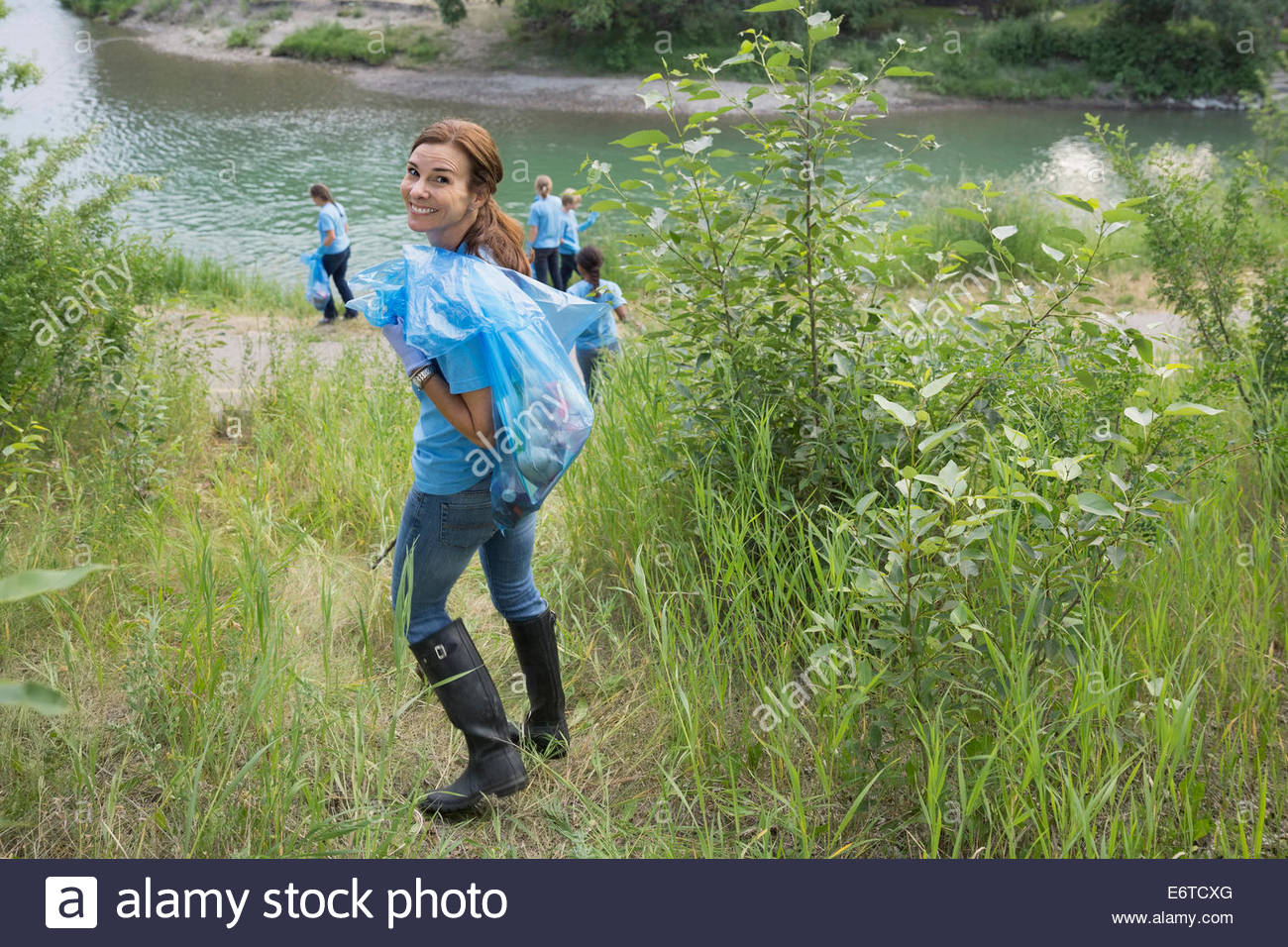 Portrait of smiling volunteer carrying garbage bag - Stock Image