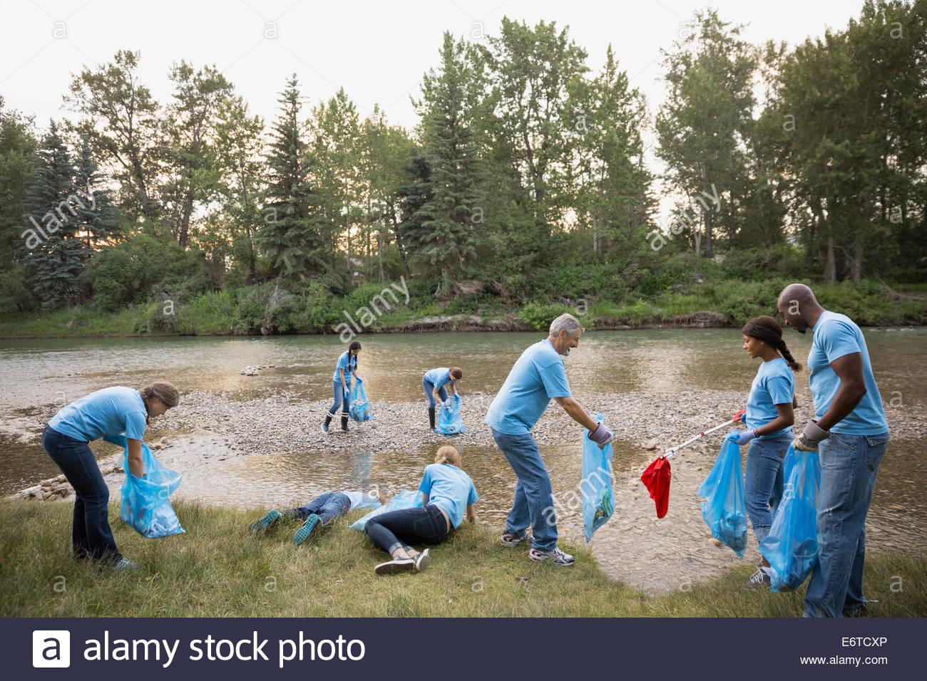 Volunteers picking up garbage at riverbank - Stock Image