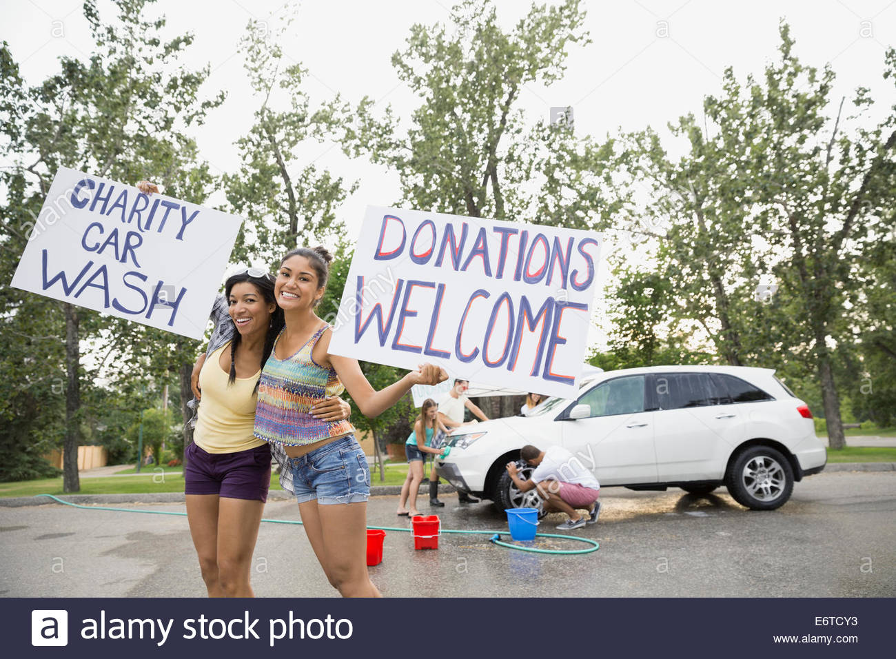 Volunteers holding charity car wash signs - Stock Image