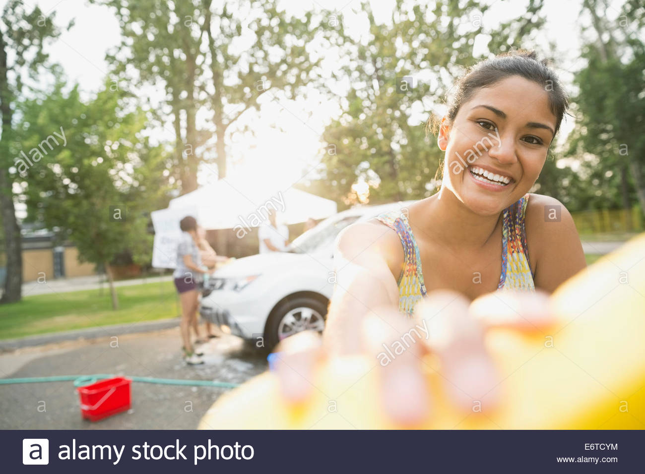 Portrait of smiling woman at car wash - Stock Image
