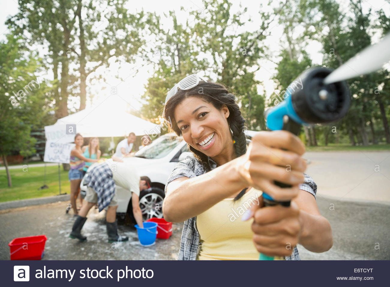 Portrait of woman using hose at car wash - Stock Image