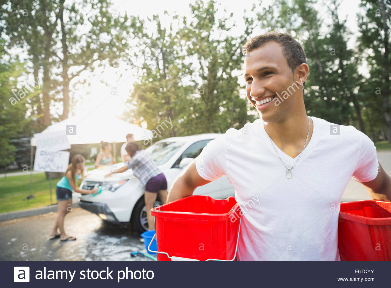 Portrait of man with buckets at car wash - Stock Image