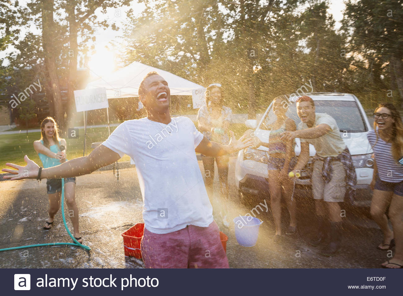 Woman spraying man with hose at car wash - Stock Image