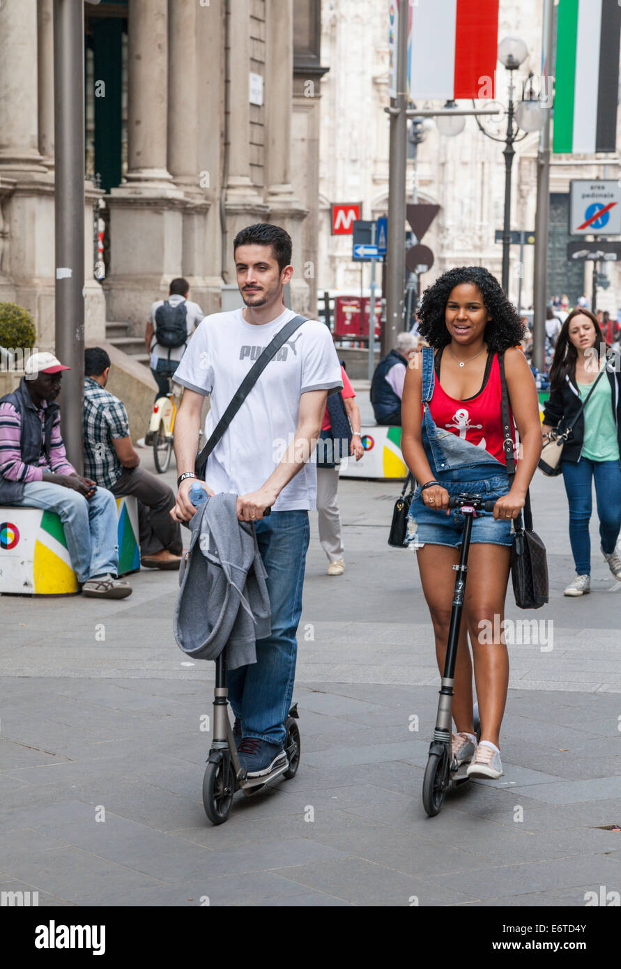 Couple on scooters in Milan, Italy - Stock Image