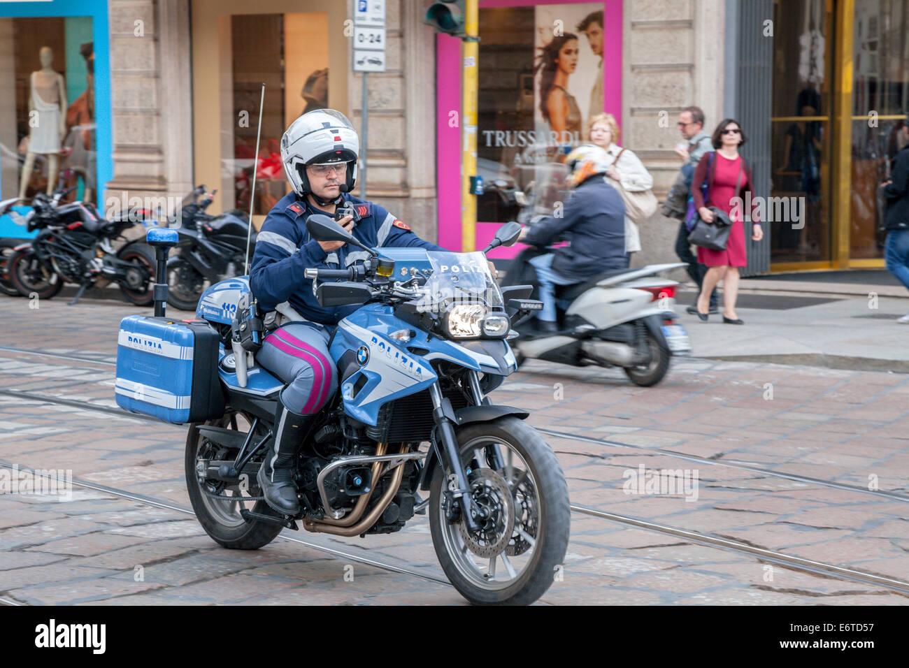 Italian Polizia motorcycle policeman looking at telephone while riding motorbike - Stock Image