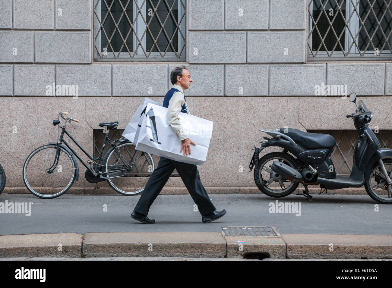 Man with shopping bags in Milan's Quadrilatero d'Oro - golden shopping rectangle - Via Monte Napoleone, Milan, - Stock Image