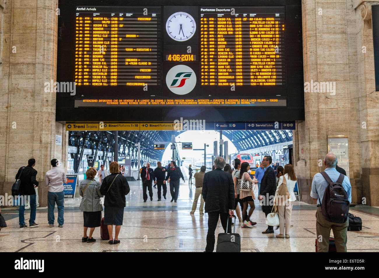 Departures electronic train board and waiting passengers, Milan Central Station, Italy - Stock Image