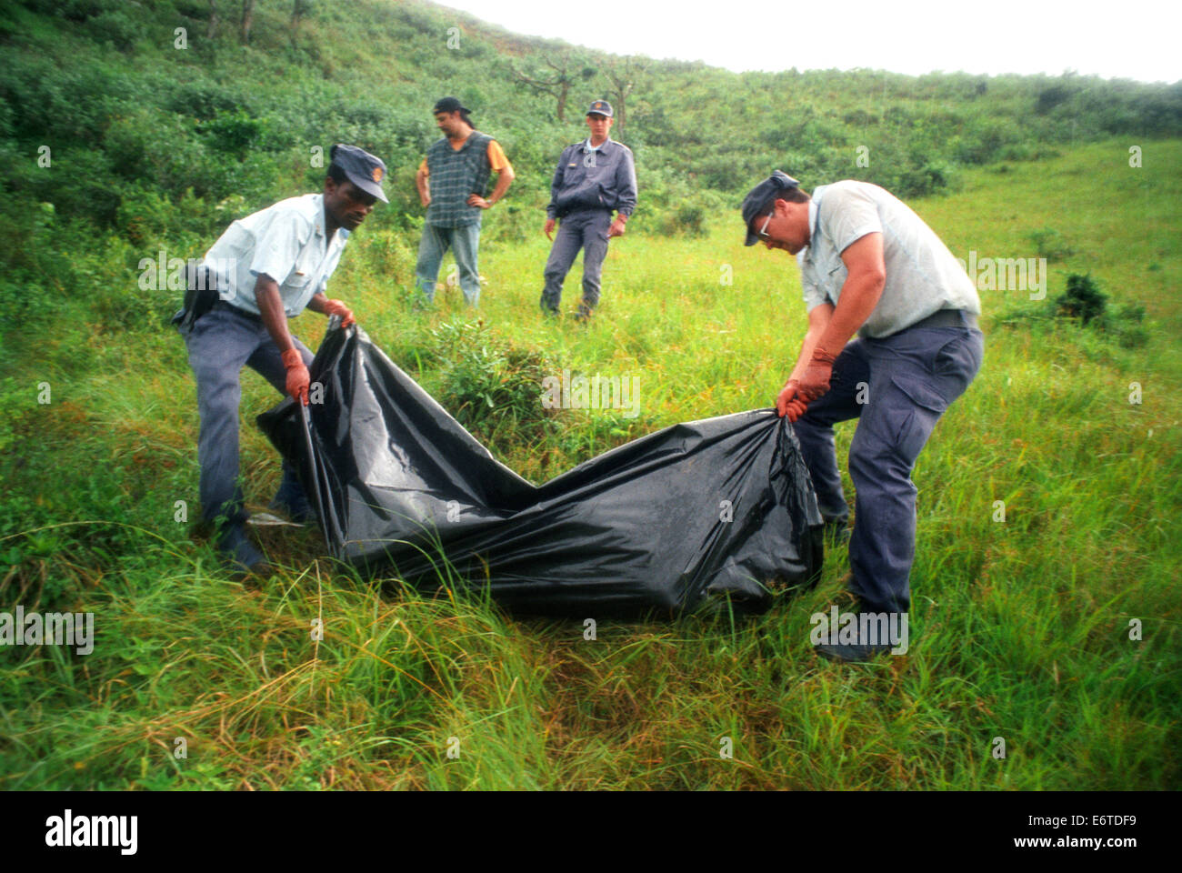 South African police recover the body of a villager near the hamlet of Shoboshobane, on the KwaZulu/Natal South - Stock Image
