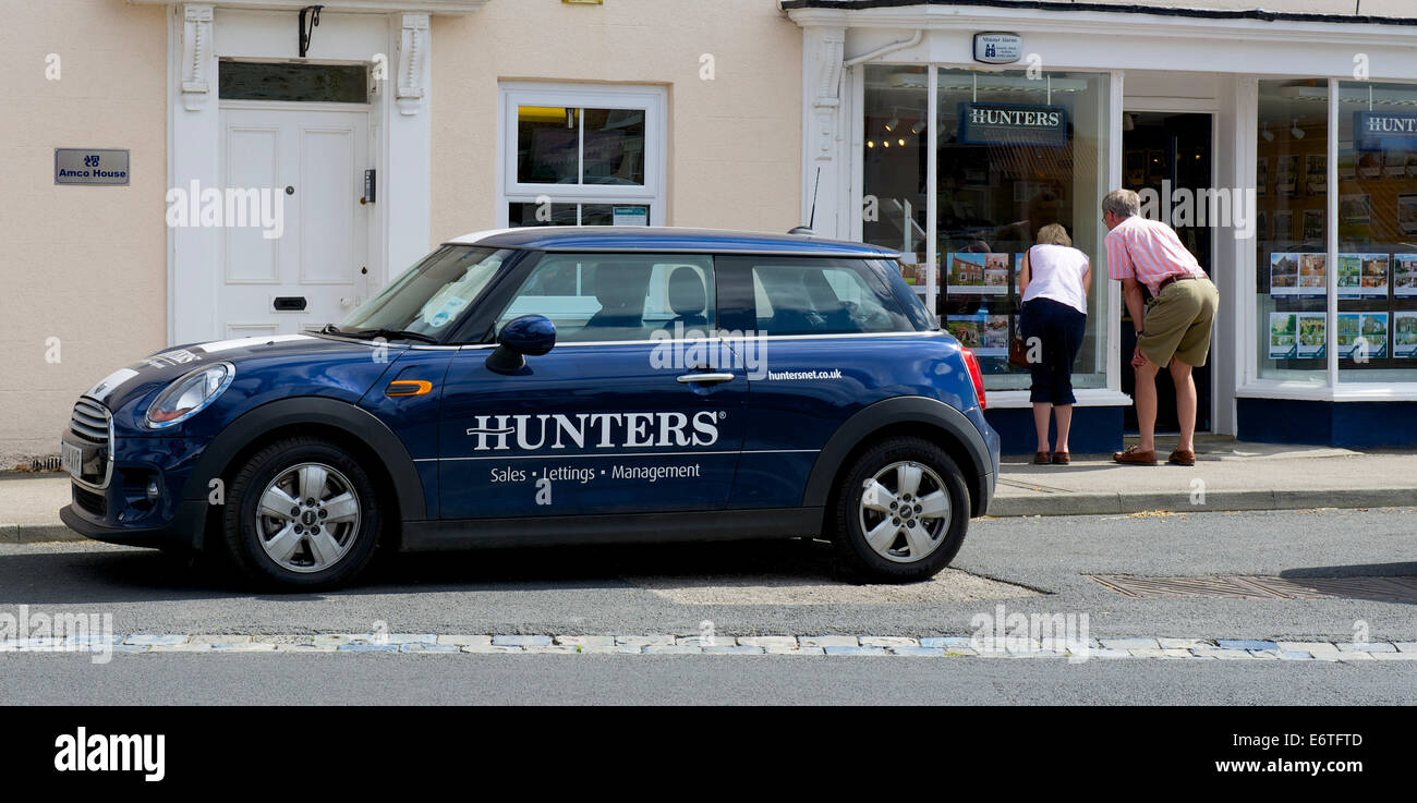 Man and woman looking into window of Hunters, estate agents, Easingwold, North Yorkshire, England UK - Stock Image
