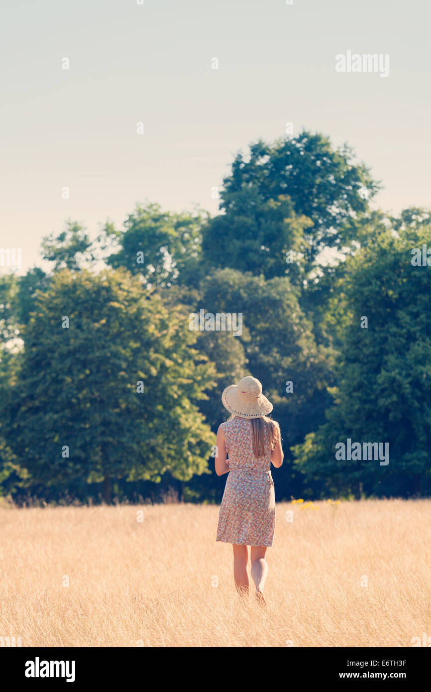 A young woman walking in a field of grass in Hyde Park, London in the English summer - Stock Image