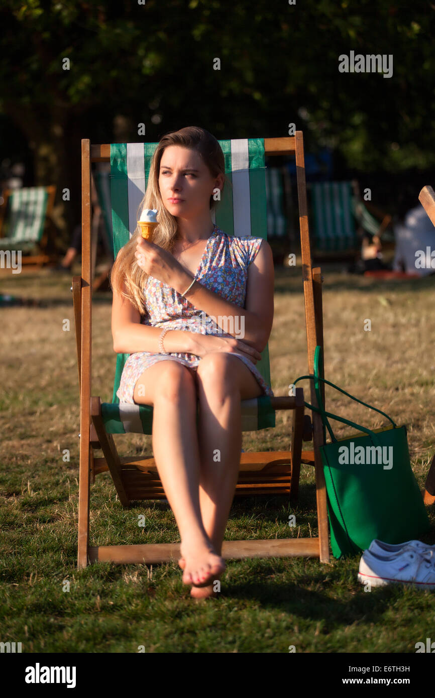 A young woman eating an ice cream in Hyde Park in Summer - Stock Image