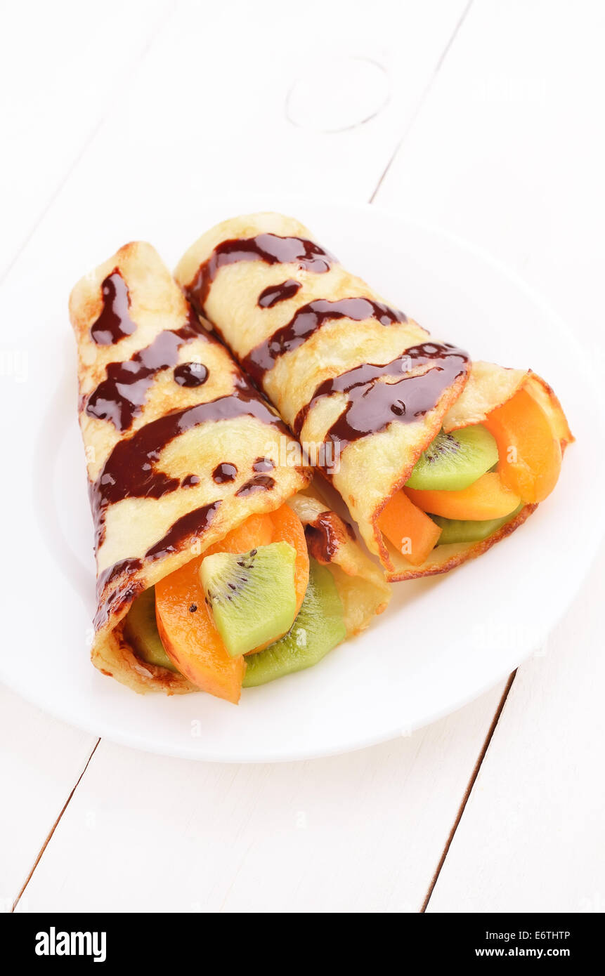 Crepes with kiwi and apricot slices on white plate - Stock Image