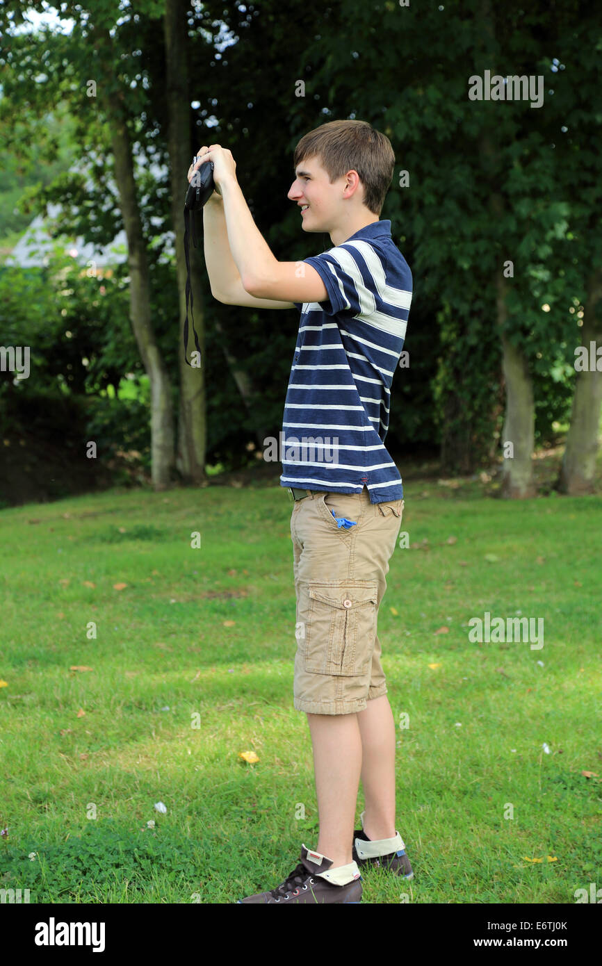 15 Year Old Boy Standing And Photographing In Park On Rue