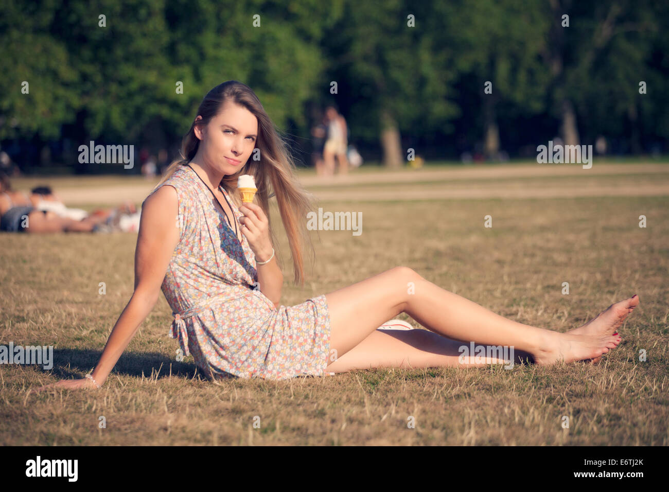 A young woman eating an ice cream cone in Hyde Park - Stock Image