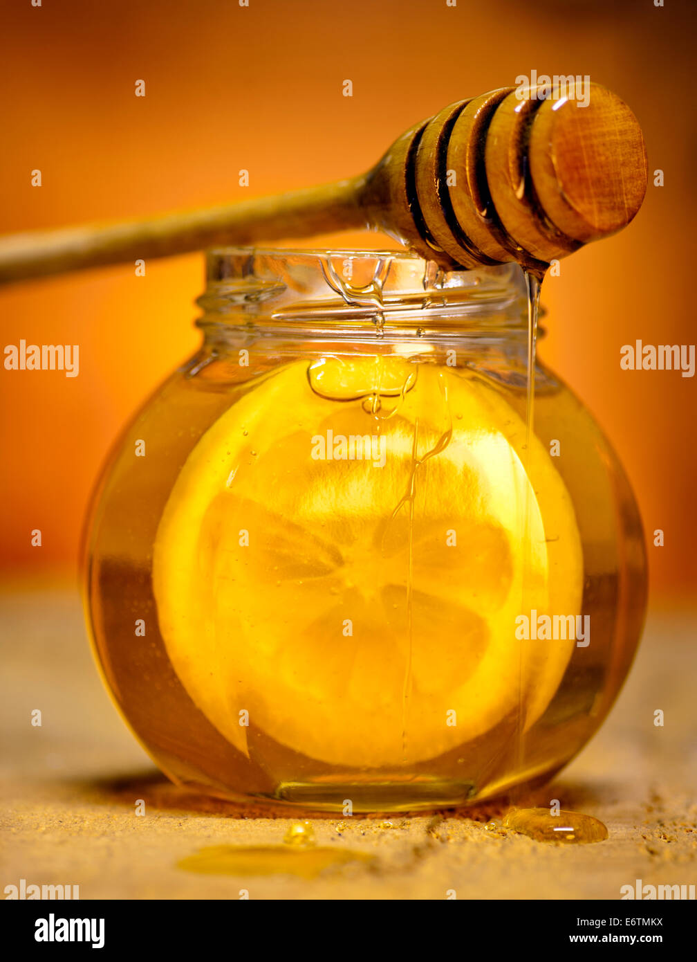 Glass jar of honey with wooden drizzler and slice of lemon on old wooden background. Stock Photo