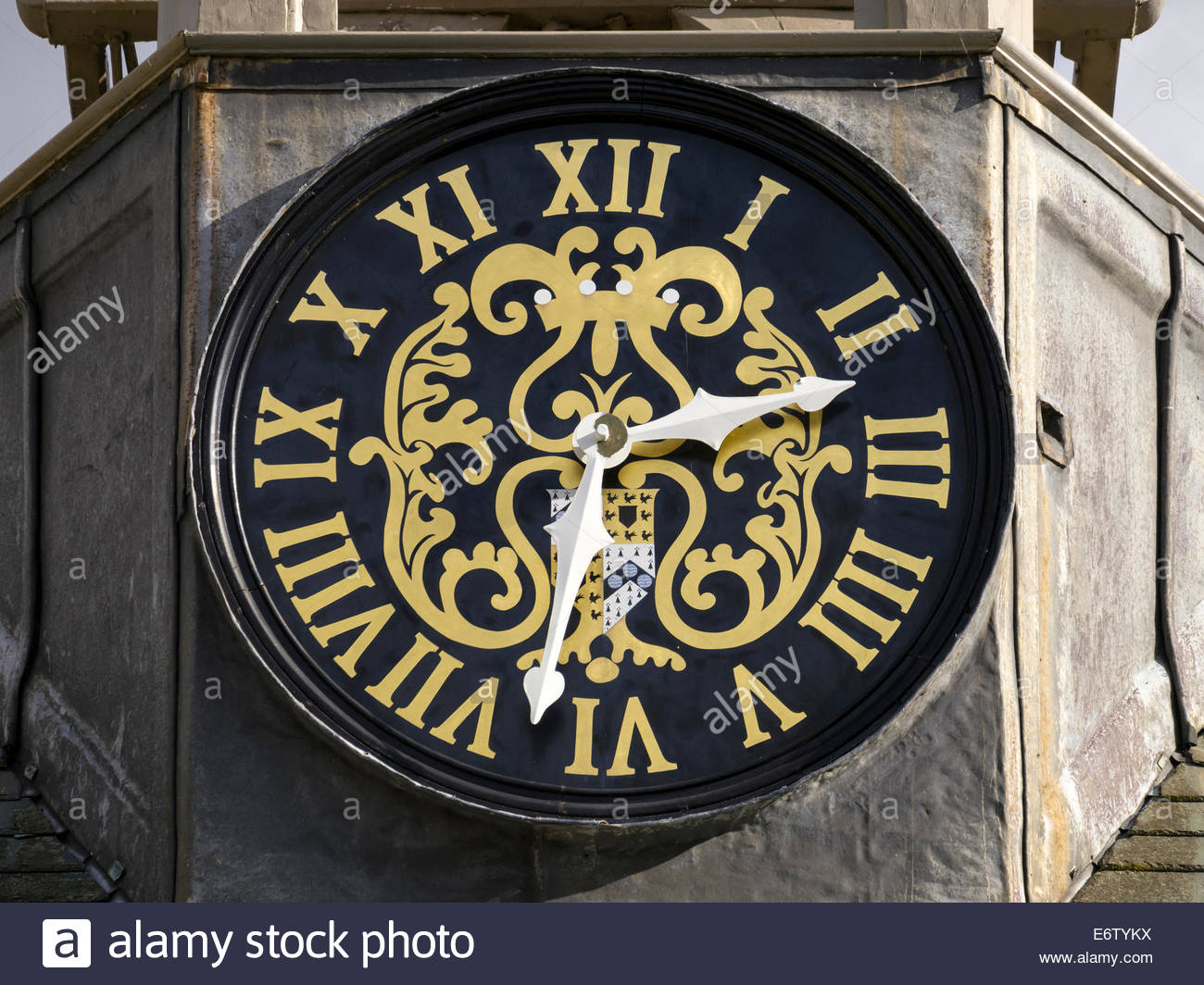 Ornate old clock face, black with gold roman numerals, Belton House, Grantham, Lincolnshire, England, UK - Stock Image